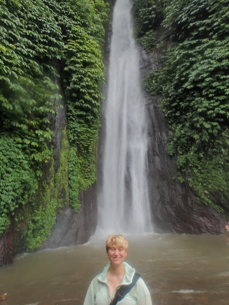 Tanah Barak Waterfall in Munduk, 75 feet tall, pouring down a cliff covered in green leafy vines. Emmons is in front, dwarfed by the waterfall.